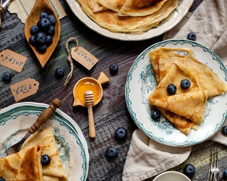 Overhead shot of thin yummy crepes with honey, blueberries on three vintage plates with green ornament on grey wooden table with honey, berries, forks, napkin. breakfast still life