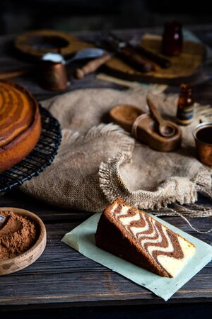 homemade baked striped slice of cake zebra from childhood stands on wicker black stand on rustic table with sackcloth, copper cups, bottles, cocoa powder, strainer, forks. selective focus
