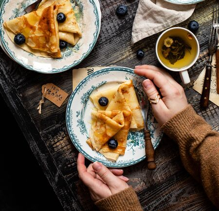 Overhead shot of thin yummy crepes with honey, blueberries on two vintage plates with green ornament in woman hands on grey wooden table with berries, forks, napkin, cup of tea. breakfast still life