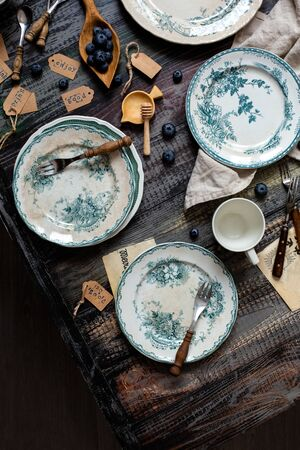 Overhead shot with still life of vintage tableware with empty plates with green floral ornament, forks, wooden bowls and letters, napkin on grey wooden table. Breakfast serving. Vintage tableware 写真素材