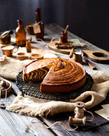 homemade baked striped cut cake zebra from childhood stands on wicker black stand on rustic table with sackcloth, spool of thread, copper cups, bottles, cocoa powder, strainer, forks. selective focus