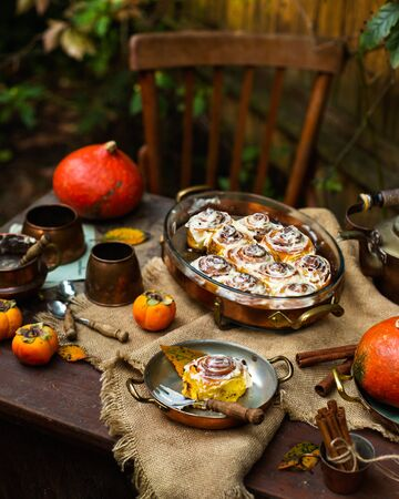 Autumn outdoor still life with homemade pumpkin cinnamon buns in oval glass dish on wooden table with copper mugs, pumpkins, persimmons, teapot, spoons, sackcloth, fall leaves opposite wooden old wall