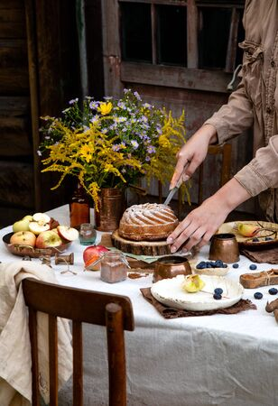 beautiful outdoor still life in country garden with bundt cake on wooden stand on rustic table with tablecloth, copper cups, berries, apples, cinnamon, plates, bouquet, chairs. woman cut the cake