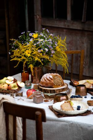beautiful outdoor still life in country garden with bundt cake on wooden stand on rustic table with tablecloth, copper cups, berries, apples, cinnamon, plates, bouquet, chairs