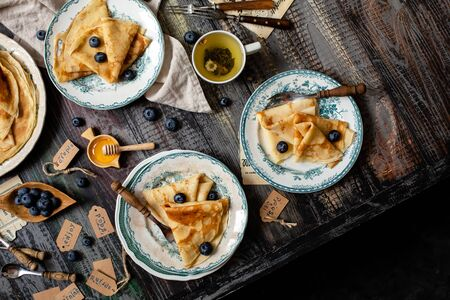 Overhead shot of thin yummy crepes with honey, blueberries on vintage plates with green ornament on grey wooden table with honey, berries, forks, napkin, cup of tea. breakfast still life