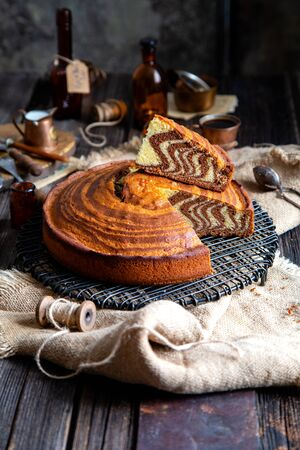 homemade baked striped cut cake zebra with slice  stands on wicker black stand on rustic table with sackcloth, spool of thread, copper cups, bottles, cocoa powder, strainer, forks. selective focus
