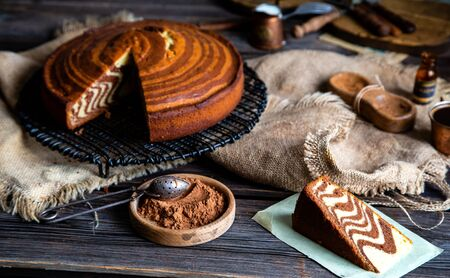 homemade baked striped cut cake zebra with slice stands on wicker black stand on rustic table with sackcloth, spool of thread, copper cups, bottles, cocoa powder, strainer, forks. selective focus Stock fotó