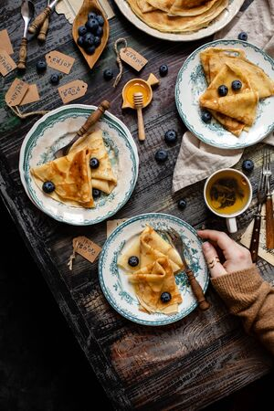 Overhead shot of thin yummy crepes with honey, blueberries on vintage plates with green ornament on grey wooden table with woman hand, honey, berries, forks, napkin, cup of tea. breakfast still life