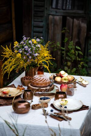 beautiful outdoor still life in country garden with bundt cake on wooden stand on rustic table with tablecloth, copper cups, teapot, berries, apples, cinnamon, plates, bouquet, chairs 写真素材