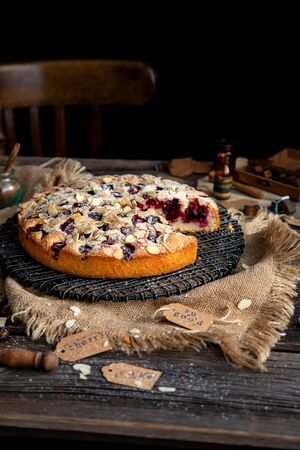 homemade tasty cut biscuit round cake with cherries, almond flakes, powdered sugar on top on black metal wicker stand on rustic wooden table with sackcloth, bottles, forks, chair next the table