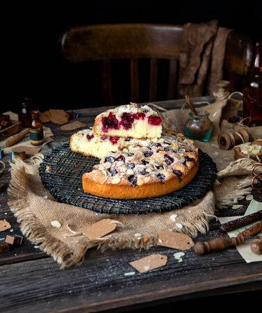 homemade tasty biscuit round cake with cherries, almond flakes, powdered sugar and slice on top on black metal wicker stand on rustic wooden table with sackcloth, bottles, forks, chair next the table