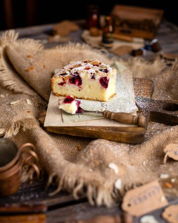 homemade tasty slice of biscuit cake with cherries, almond flakes, powdered sugar on top on wooden board on rustic wooden table with sackcloth, bottles, forks Stok Fotoğraf