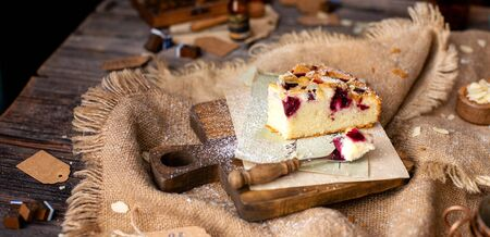 homemade tasty slice of biscuit cake with cherries, almond flakes, powdered sugar on top on wooden board on rustic wooden table with sackcloth, bottles, forks Stock fotó