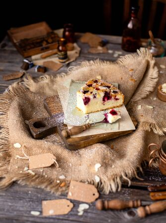 homemade tasty slice of biscuit cake with cherries, almond flakes, powdered sugar on top on wooden board on rustic wooden table with sackcloth, bottles, forks, chair next the table Stok Fotoğraf