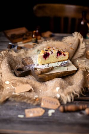 homemade tasty slice of biscuit cake with cherries, almond flakes, powdered sugar on top on wooden board on rustic wooden table with sackcloth, bottles, forks, chair next the table Stock fotó