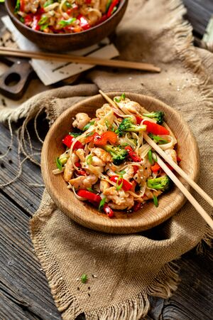 homemade tasty wok noodles with fried chicken fillet, broccoli, red paprika, green onion, sesame in wooden bowls on rustic table with chopsticks, sackcloth, selective focus Stock fotó