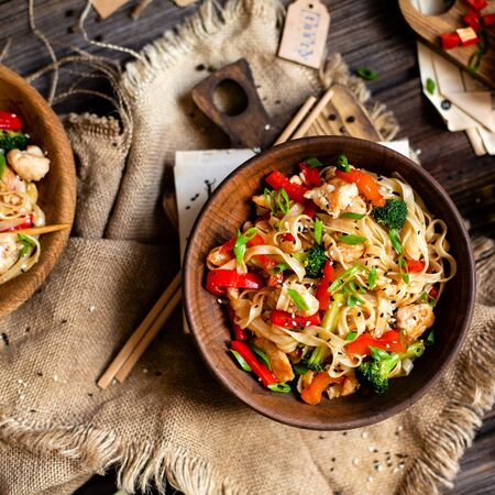 homemade tasty wok noodles with fried chicken fillet, broccoli, red ball pepper, green onion, sesame in two wooden bowl on rustic table with sackcloth, board with cut pepper, oil, chopsticks, top view Foto de archivo - 129826967