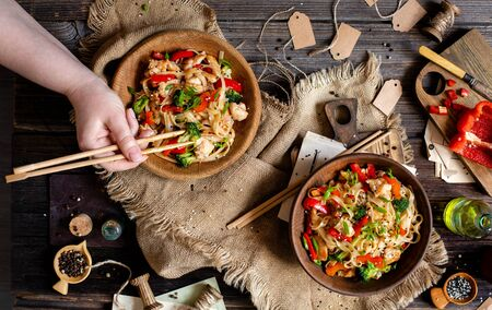 homemade tasty wok noodles with fried chicken fillet, broccoli, red paprika, green onion, sesame in two wooden bowls, woman hand with chopsticks on rustic table with sackcloth, oil, knife, top view Foto de archivo - 129826972