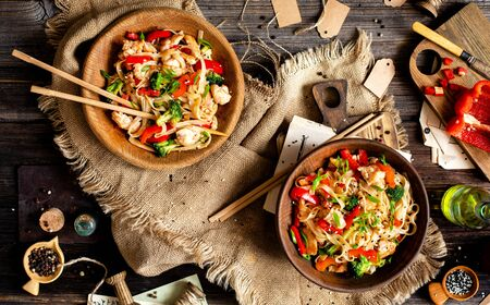 homemade tasty wok noodles with fried chicken fillet, broccoli, red paprika, green onion, sesame in two wooden bowls on rustic table with sackcloth, cut pepper, oil, knife, chopsticks, top view Foto de archivo - 129826976