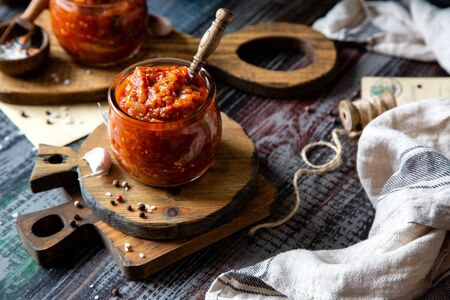 two glass jars with home made red vegetable caviar, ratatouille, ragout on wooden brown boards on rustic dark grey table with wicker straw basket, garlic, pepper, utensils, napkin, selective focus