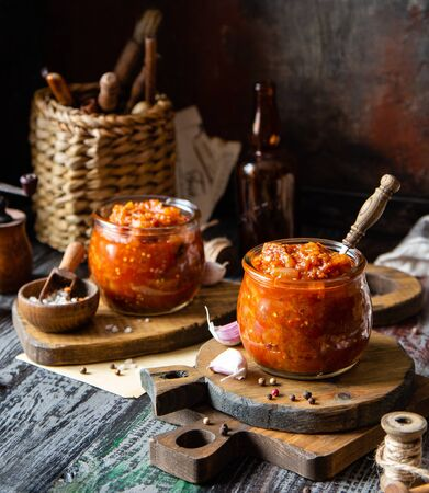 two glass jars with home made red vegetable caviar, ratatouille, ragout on wooden brown boards on rustic dark grey table with wicker straw basket, garlic, pepper, utensils, napkin, selective focus Stockfoto - 129269010