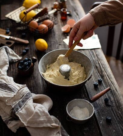 woman hold spatula and stow dough in bund pan, process of preparation sponge lemon cake on rustic wooden table with metal basket with eggs, lemons, forks, blueberries, flour strainer, grey napkin Stok Fotoğraf
