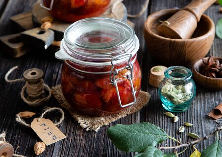 Two glass jars with homemade canned plums jam, marmalade, jelly on rustic wooden table with cardamon, cinnamon,  anise, bowl of plums, spice mortar, spool of thread, bones and branch with green leaves 스톡 콘텐츠