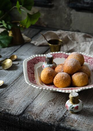 Homemade small round ball donuts sprinkled with powdered sugar on vintage plate with pink ornament on grey wooden table with vintage powder shakers, towel, brass spoons, glasses, branch with leaves