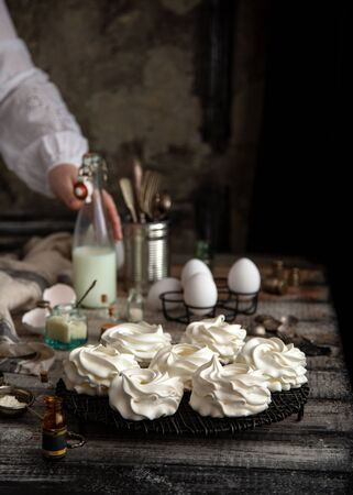 Homemade white mini meringue desserts pavlova on Wicker metal stand on grey wooden table with bottles, eggs, towel, jar with kitchen utensils, spices, opposite old concrete wall. Woman hold bottle