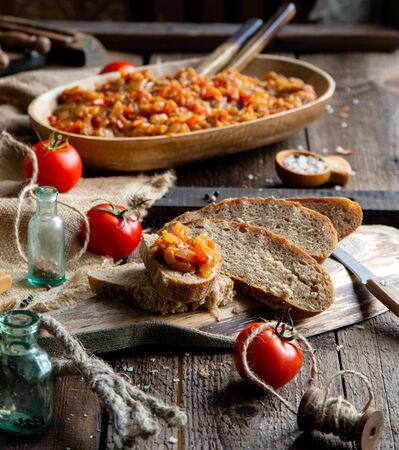 Homemade tasty orange vegetable caviar, ratatouille or ragout on slices of bread and in oval wooden dish on rustic brown table with old bottles, bowl with spices, tomatoes and sackcloth