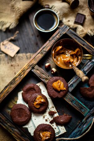 Overhead shot of homemade chocolate tasty cookies with caramel or boiled condensed milk on dark blue wooden board with copper cup with caramel on rustic table with sackcloth, cup of coffee, chocolate