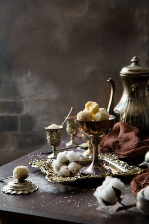 Homemade white truffle candies in coconut chips on silver vintage cup on vintage tray standing on brown wooden table with cups, antique teapot, cotton, brown textile opposite grey concrete brick wall