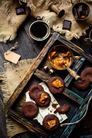 Overhead shot of homemade chocolate cookies with caramel or boiled condensed milk on dark blue wooden board with copper cup with caramel on rustic table with sackcloth, cups with coffee, chocolate 写真素材