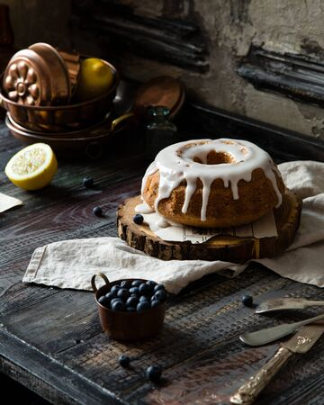 Homemade delicious bundt cake (with hole) with white glaze on top on wooden stand on rustic table with vintage copper cup of blueberries, lemon, towel, copper baking pans. Beautiful vintage still life 写真素材