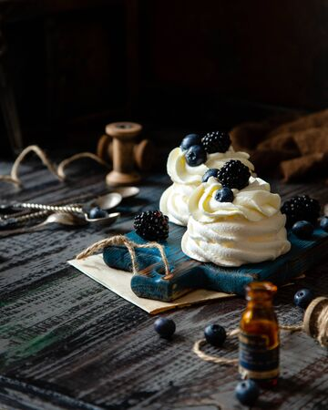 Two homemade white mini desserts pavlova on wooden blue board with whipped cream and blueberries, blackberries on rustic table with berries, old bottles, spoons, spool of thread, brown towel