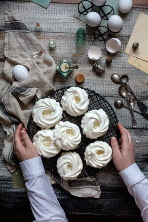 Overhead shot of homemade white mini meringue desserts pavlova on wicker stand with women hands on grey wooden table with bottles, eggs on black stand, towel, spoons, weights, egg shells Reklamní fotografie