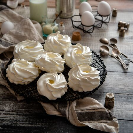 Homemade white mini meringue desserts pavlova on wicker metal stand on grey wooden table with bottle of milk, eggs in black metal stand, towel, spices, spoons, weights