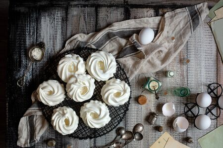 Overhead shot of homemade white mini meringue desserts pavlova on wicker metal stand on grey wooden table with bottles, eggs on black stand, towel, spices, spoons, weights, egg shells Reklamní fotografie