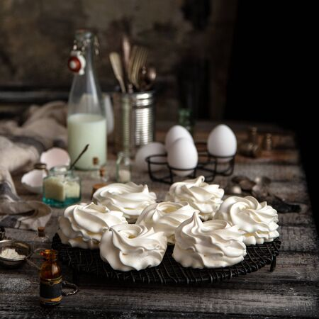 Homemade white mini meringue desserts pavlova on Wicker metal stand on grey wooden table with bottles, eggs, towel, jar with kitchen utensils, spices, strainer, spoons opposite old concrete wall