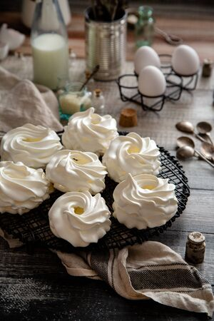 Homemade white mini meringue desserts pavlova on Wicker metal stand on grey wooden table with bottles, eggs, towel, jar with kitchen utensils, spices, strainer, spoons, weights