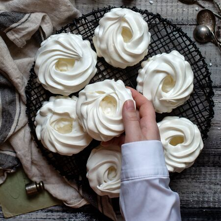 Overhead shot of homemade white mini meringue desserts pavlova on wicker stand with women hand on grey wooden table with  towel, spoons, weights. Women hand hold cake