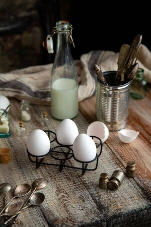 Still life with vintage bottle of milk, black metal stand with eggs, jar with kitchen utensils on grey wooden table with bottles of spices, towel, spoons, weights opposite concrete wall. Ingredients Reklamní fotografie