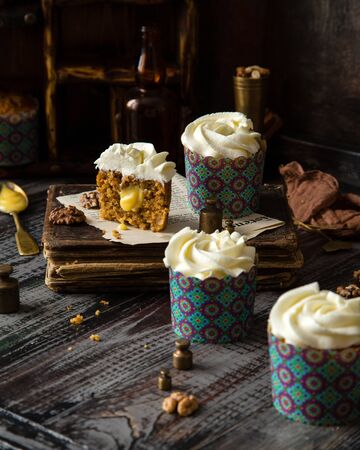 Delicious homemade cut of carrot cupcakes with white beautiful icing and orange filling standing on rustic wooden table with vintage book, spoons, brown textile, brass weights, walnuts, cinnamon