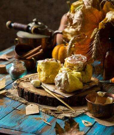 cinnamon rolled pumpkin buns with white sticky glaze on top on wooden stand on rustic blue wooden table with copper cup of icing, pumpkins, autumn leaves, cinnamon, selective focus, thanksgiving