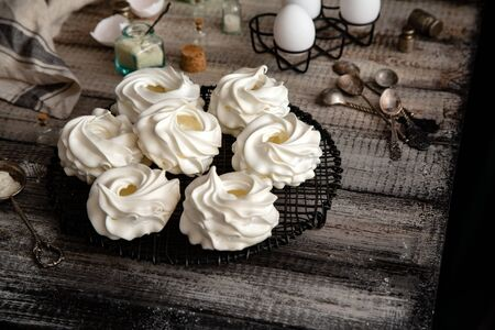 Homemade white mini meringue desserts pavlova on Wicker metal stand on grey wooden table with bottles, eggs, towel, jar with kitchen utensils, spices, strainer, spoons, strainer