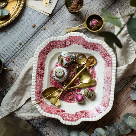 Overhead shot of vintage plate with pink ornament with brass spoons, strainers and chinese tea balls on wooden grey table with brass teapot, cups of brown sugar, branch with leaves and towel