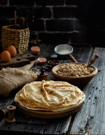 Homemade stack of crepes on wooden plate stand on rustic table with plate of ground fried meat, egg stand, eggs, sackcloth, strainer with flour, pepper, wicker stand with utensils opposite brick wall