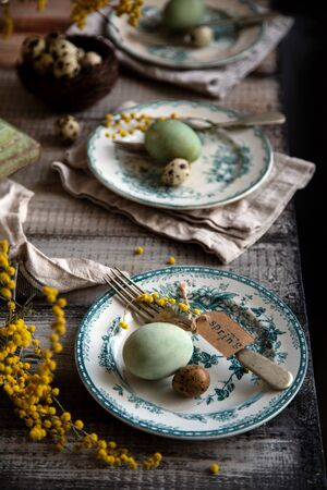Orthodox Easter table setting with three vintage plates with green ornament, forks, dyed green eggs, nest with quail eggs, yellow flowers, tag with word easter on grey wooden table with grey towels
