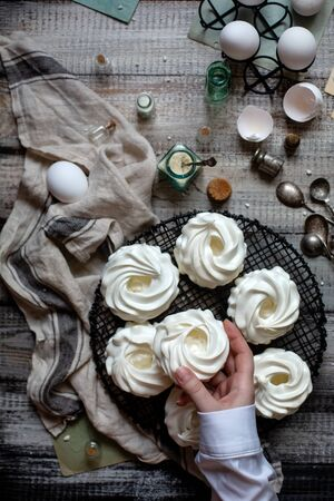 Overhead shot of homemade white mini meringue desserts pavlova on wicker stand with women hand on grey wooden table with bottles, eggs on black stand, towel, spoons, weights, egg shells
