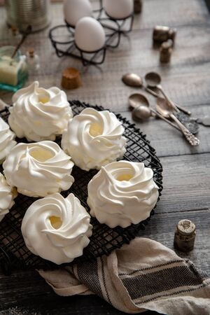 Homemade white mini meringue desserts pavlova on Wicker metal stand on grey wooden table with bottles, eggs, towel, jar with kitchen utensils, spices, strainer, spoons. Back light